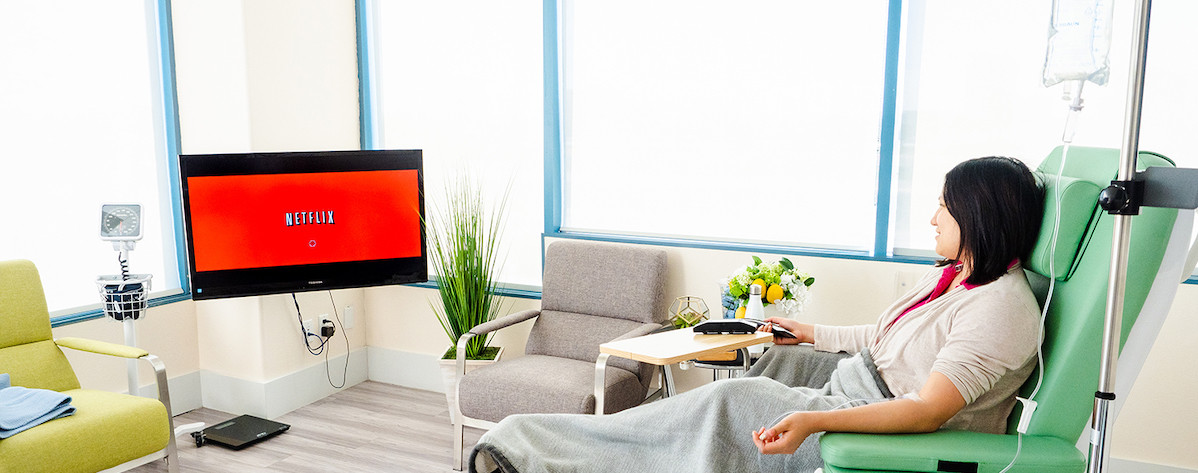 Patient watching Netflix during her infusion therapy treatment