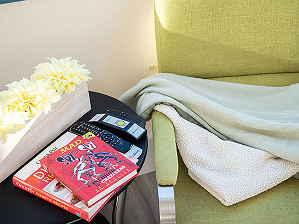 Infusion Center chair with blanket next to books and remote control