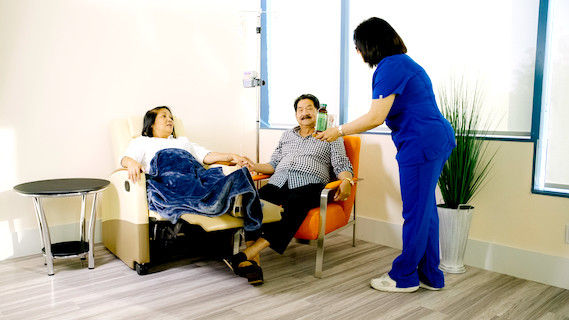 Infusion nurse offering drinks to patient and guest