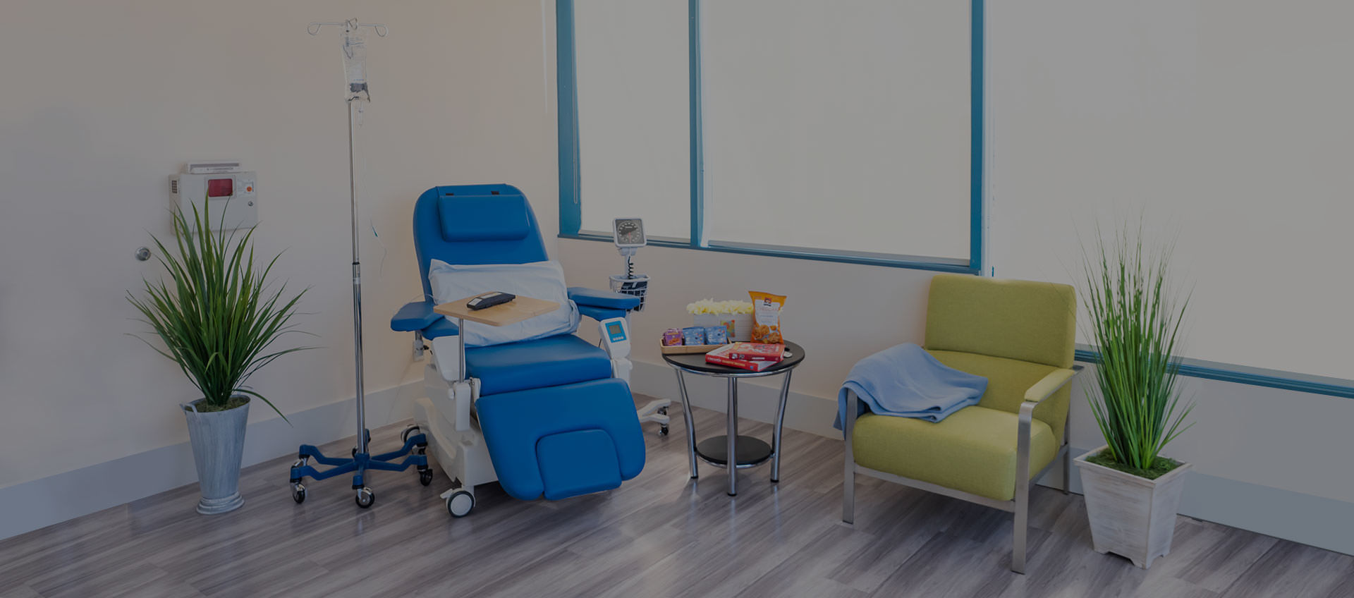 State-of-the-art infusion center suite with reclining infusion chair, guest chair, snacks, books and decoration